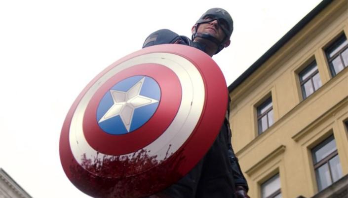 Imagem: o personagem Agente Americano, um homem em traje de Capitão América, um traje azul com um capacete em formato de A e com formato de estrela e um escudo redondo com listras vermelhas, brancas e no centro o círculo azul com uma estrela branca no centro e manchado de sangue.
