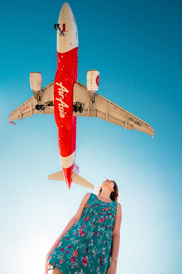 A girl looking up to an Airasia plane
