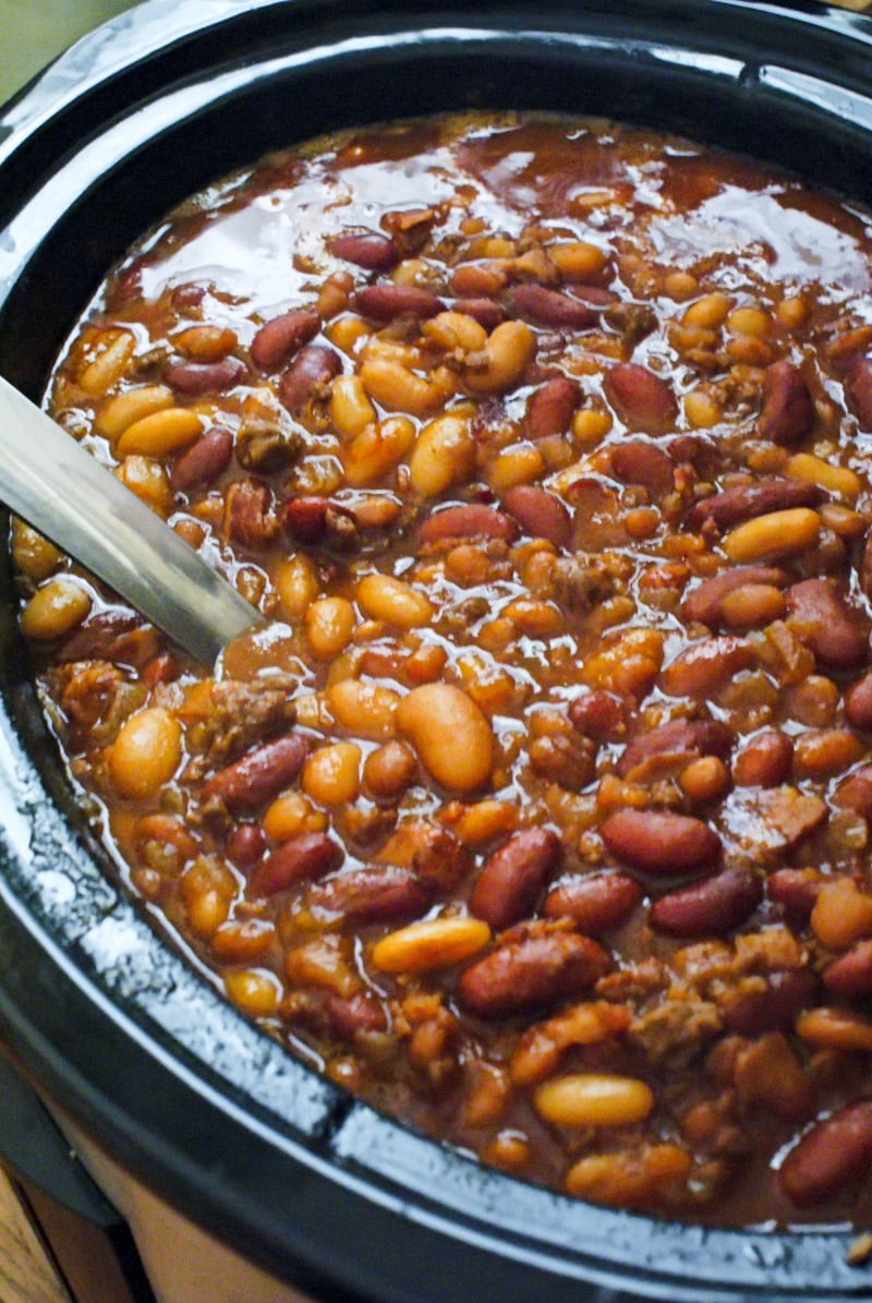 Crock Pot Cowboy Beans are a hearty and filling side dish made with a pound a beef, a pound of bacon, and three kinds of beans, all slow-simmered in a sweet and tangy brown sugar molasses sauce.  #bakedbeans #cowboybeans #sidedish #crockpot