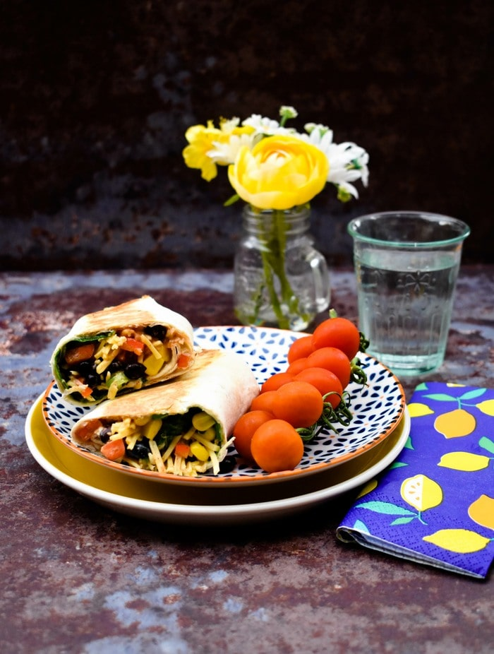 Tex Mex Cheese Wrap on a yellow plate served with cherry tomatoes and a glass of water