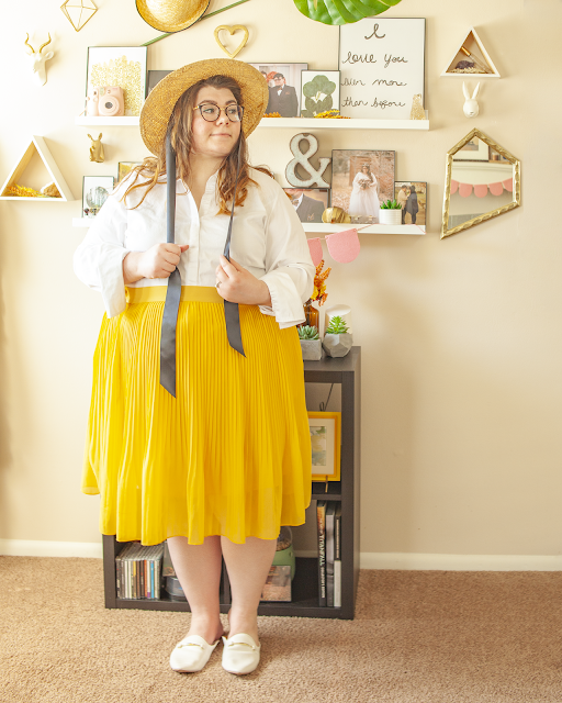An outfit consisting of a straw boater hat with black satin ribbons not tied, a white button down blouse with the first two buttons unbottoned and the sleeves folded up tucked into a mustard yellow pleated midi skirt and white mules.
