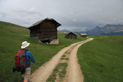 Walking on the south, southeast, and east of Sass de Putia with its characteristic wooden structures.