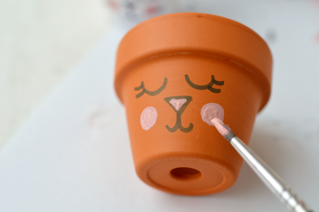 Painting the face of a DIY Bunny Egg Cup made from a mini planter by Motte's blog