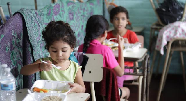 Estas niñas salvadoreñas eran beneficiarias de los almuerzos escolares. Ahora esas raciones de alimentos se preparan  para que los niños se los lleven a sus casas. PMA/David Fernandez