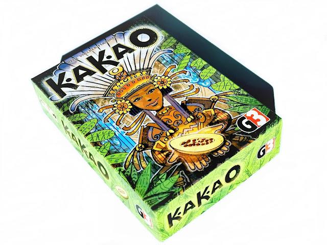 na zdjęciu pudełko gry kakao, okładka przedstawia piękna indiankę z kolorowym, kwiecistym pióropuszem na głowie, ziarnem kakaowca w rękach, otoczoną przez roślinność