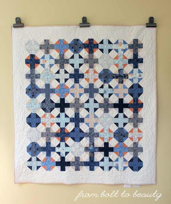 A full flat shot of a plus-sign quilt in modern fabrics