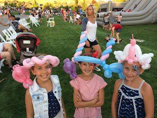 Three cute girls with their faces painted wearing ballon hats and animals