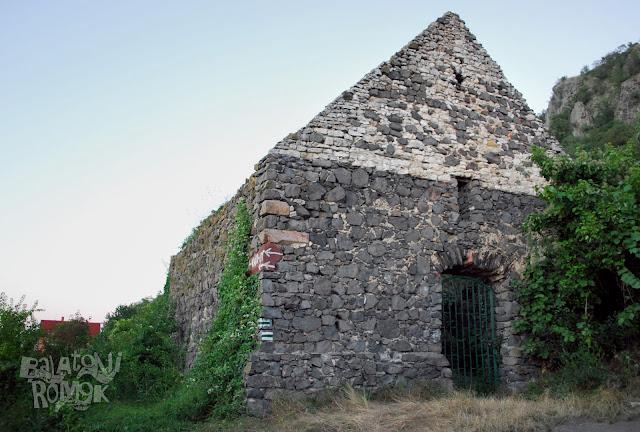 Bazaltkőből rakott templomfal, a nyugati ajtónyílással. A fal helyenként borostyánnal benőve. Jobbra a Csobánc bazaltormai.