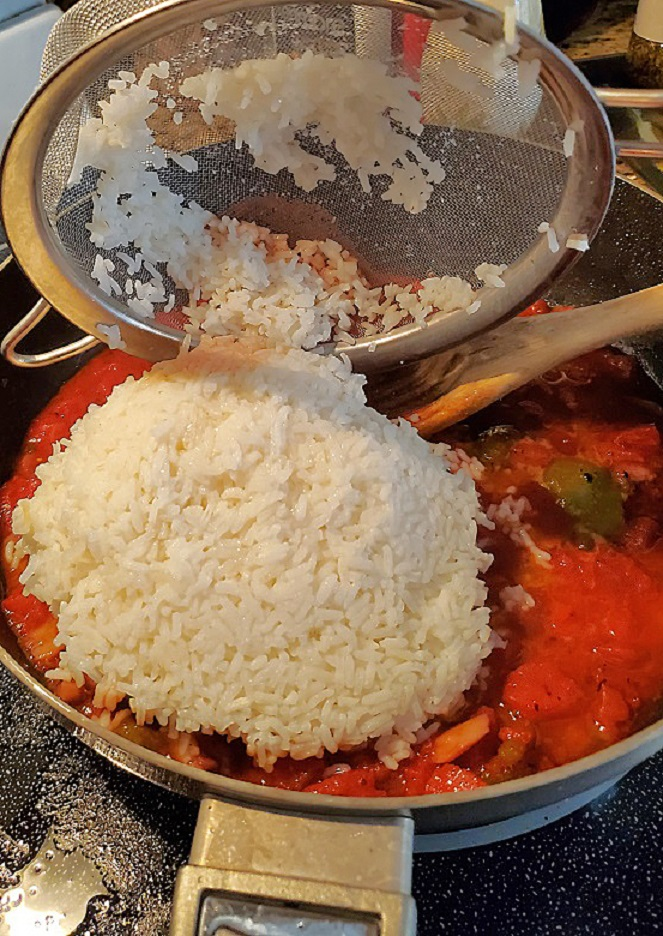 this is around 3 cups of white rice being poured into a tomato sauce for Spanish Rice made Italian style