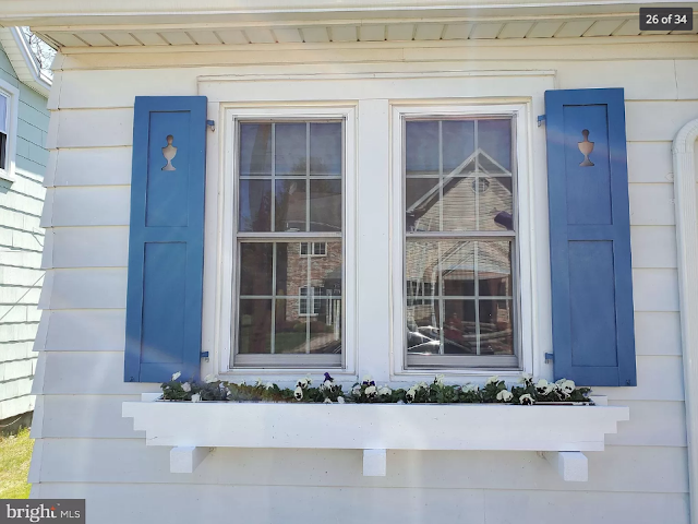 blue shutters on the front of the house with a small urn shape cut-out