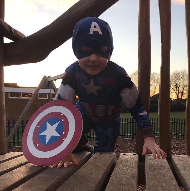 Little boy dressed as Captain America playing on a park