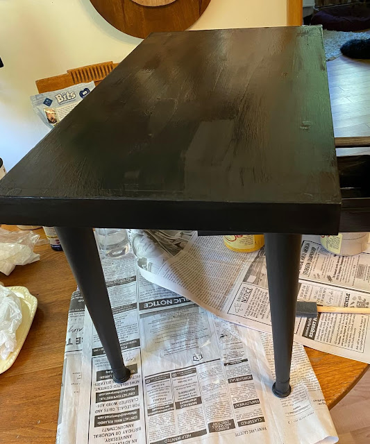 Photo of a coffee table being painted black.
