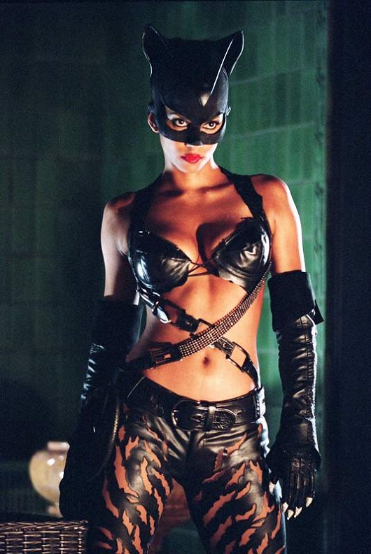 Halle Berry in Catwoman suit: black gloves, cat-eared cowl, shredded-looking black leather leggings, bra top and harness