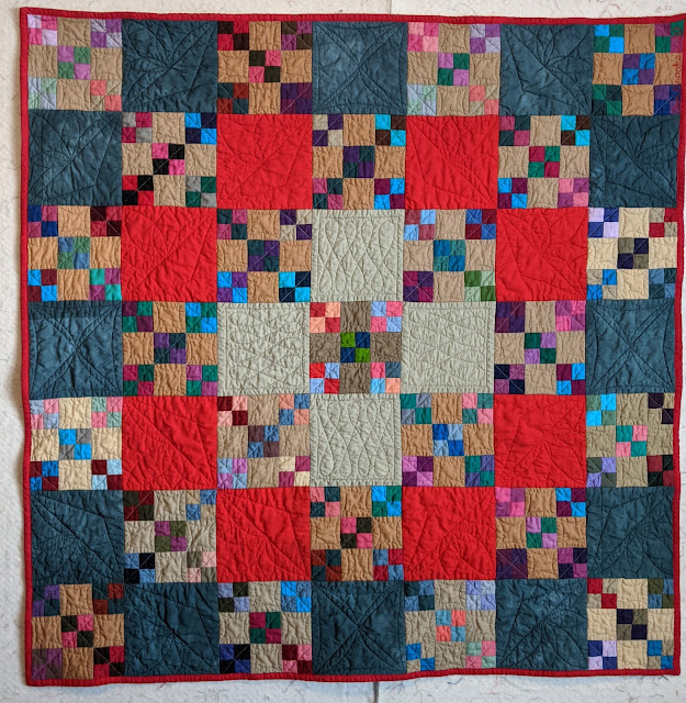 Small nine-patch blocks alternate with cadet blue, bright red, and tan solid fabric blocks and highlight a variety of free motion quilting.