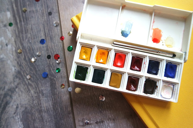 a white palette with 12 watercolours sat on a yellow sketch book