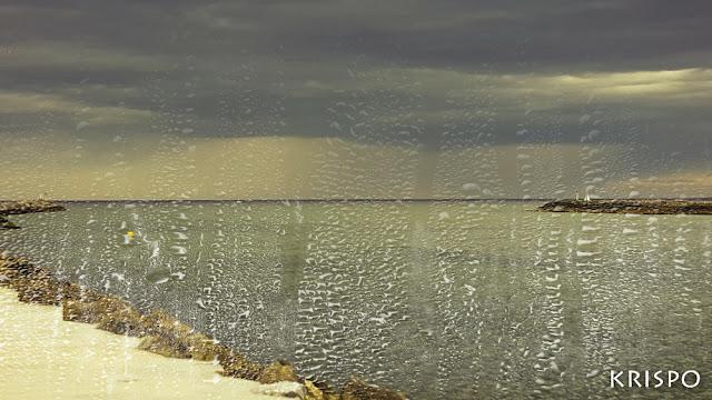 mar y horizonte a traves de una ventana mojada en un día de lluvia