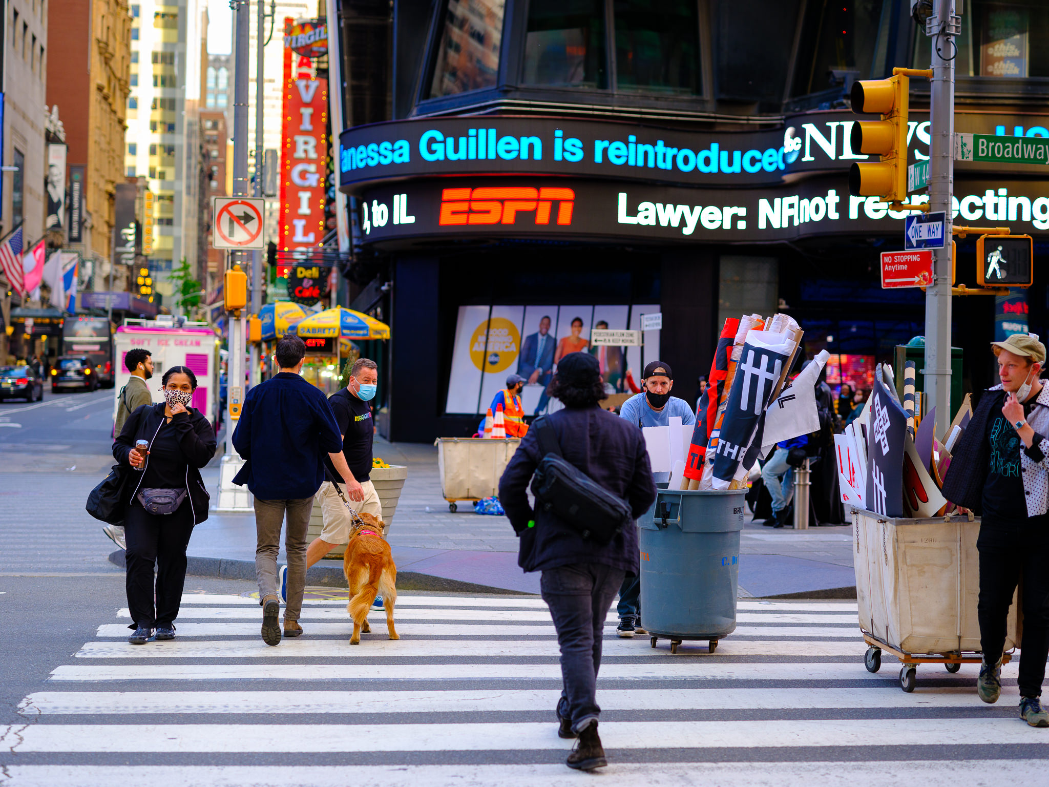 a color photo of people crossing the street in times square new york city