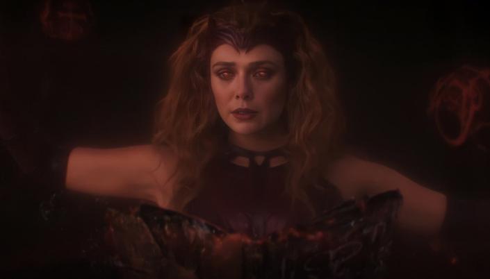 Imagem: Uma projeção astral de Wanda caracterizada como Feiticeira Escarlate. Ela está com o cabelo esvoaçante e armado, usa uma roupa vermelha que é um espécie de regata de couro e usa luvas que sobem até o meio do braço. Ela está lendo um livro que flutua na frente dela. É o livro darkhold: um grimório de magia e seus olhos estão vermelhos enquanto ela lê. Seus braços estão levantados e ela faz símbolos com a mão e Runas de energias voam ao redor dela.