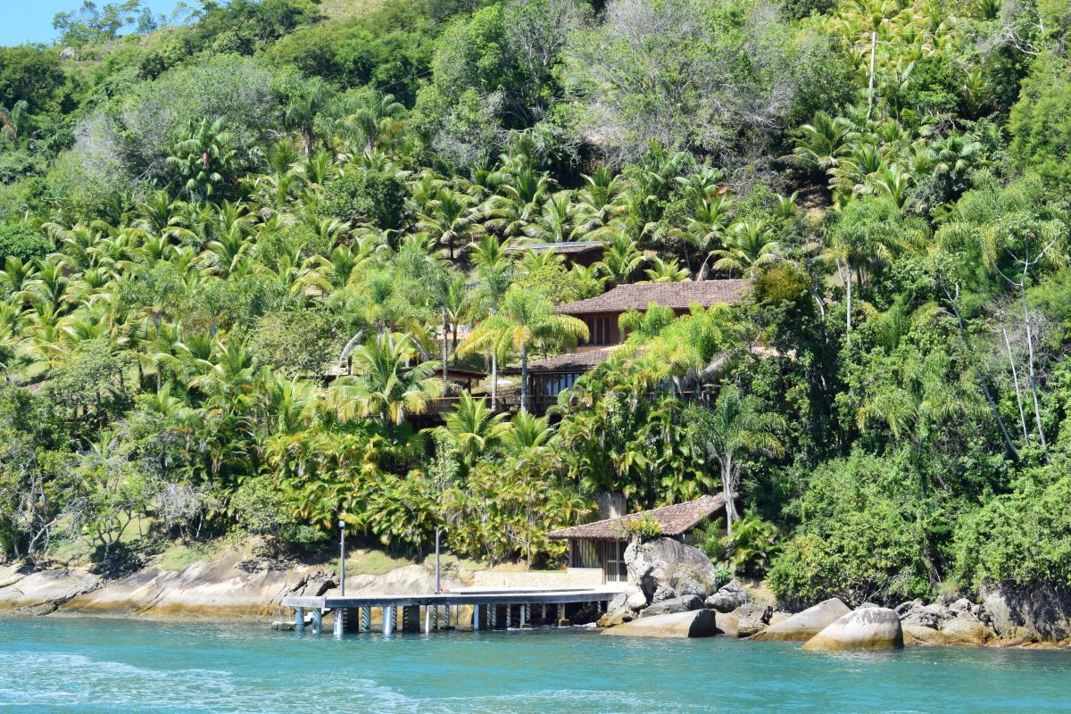 vila de pescadores em ilha pequena em mar aberto de águas esverdeadas