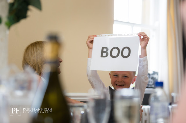 son holding a sign saying boo during wedding speech