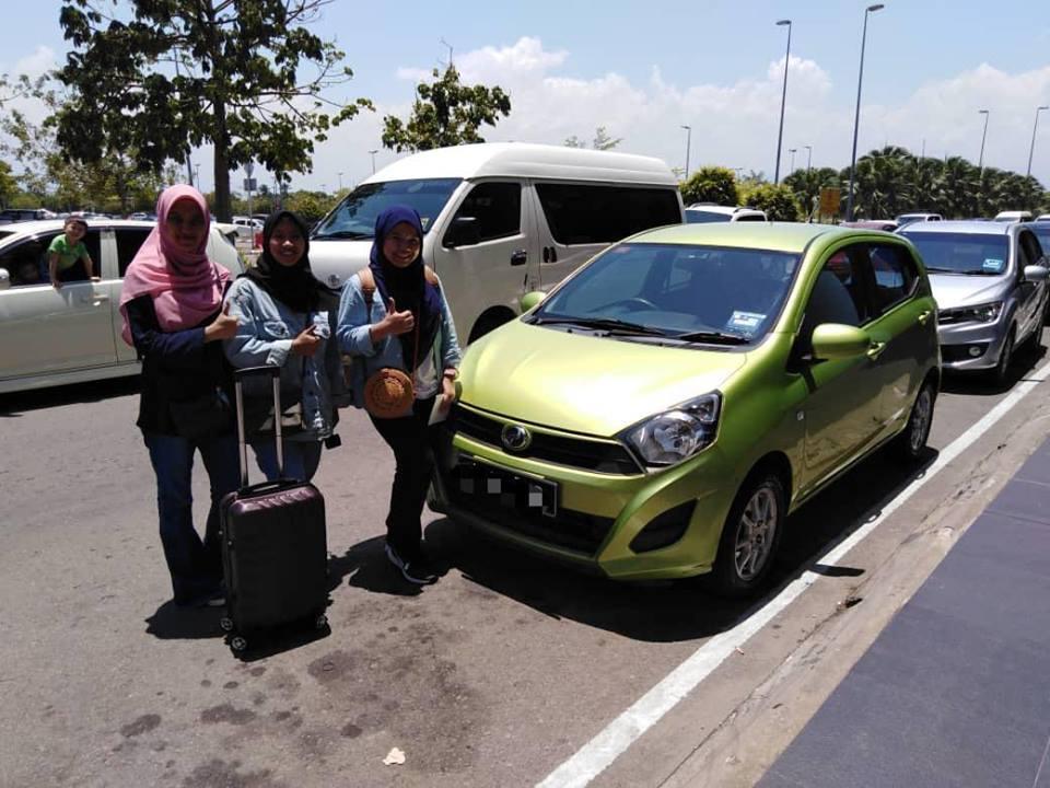 sewa kereta axia di kota kinabalu sabah. 3 sekawan wanita sewa kereta Perodua Axia berwarna hijau dan terima kereta di kawasan luar parkir lapangan terbang antarangbangsa Kota Kinabalu Sabah.