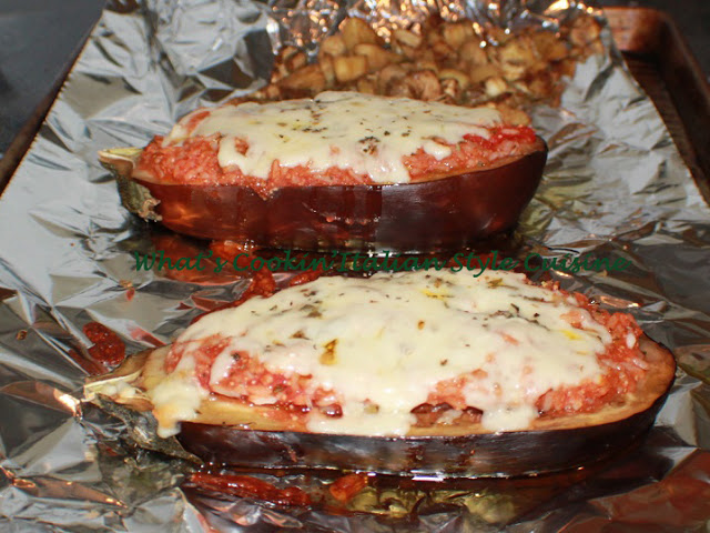 these are two roasted and stuffed eggplants called eggplant boats with cheese on top melted and tomato sauce