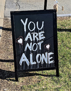 "A sandwich board sign with the saying, ""You are not alone"" written on it."