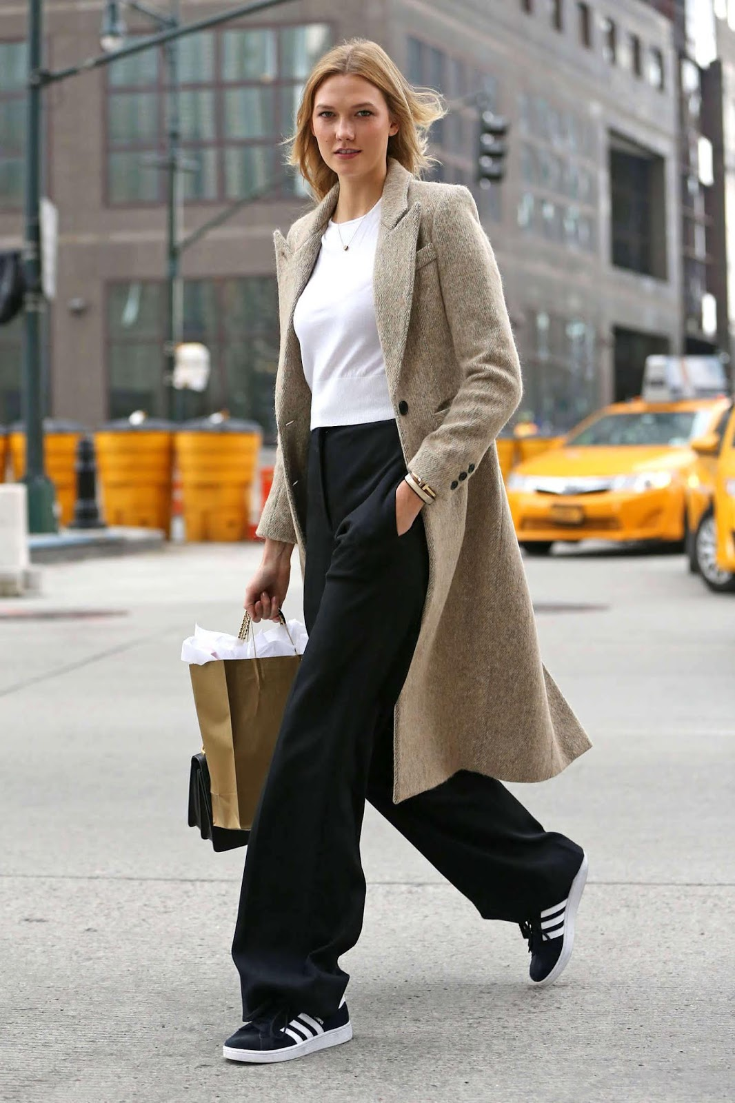 Spring Transitional Outfit Idea — Karlie Kloss in a beige coat, white sweater, black wide-leg pants, and Adidas sneakers