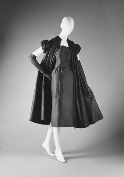 Simple Black strapless dress paired with taffeta coat displayed on mannequin from House of Dior 1951 Sylvie