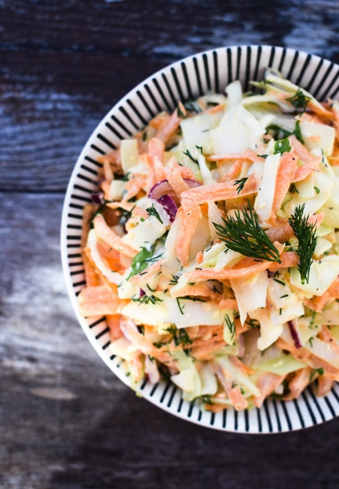 An overhead shot of carrot coleslaw in a white bowl