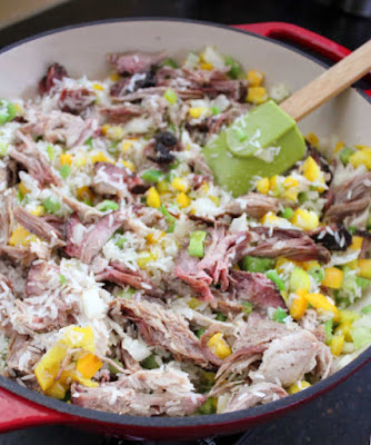 toasting rice with pulled pork, peppers and onions in skillet