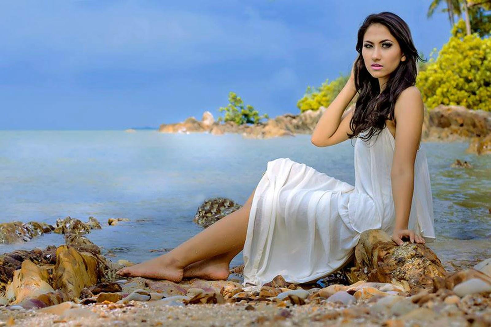 Model cewek Igo Gaun putih di pantai manis