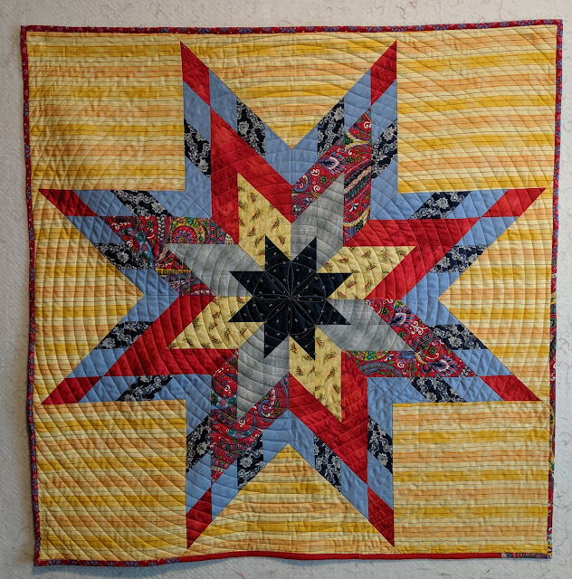 Blue, red, and yellow Lone Star quilt on yellow striped background