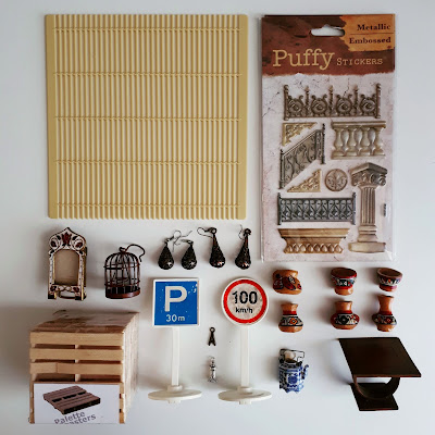 Flat lay of various 1/12 scale miniature items including an oak coffee table, peruvian pots, pallets, road signs, and puffy stickers.
