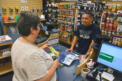 Photo of a student shopping at bookstore.  Clerk assisting.
