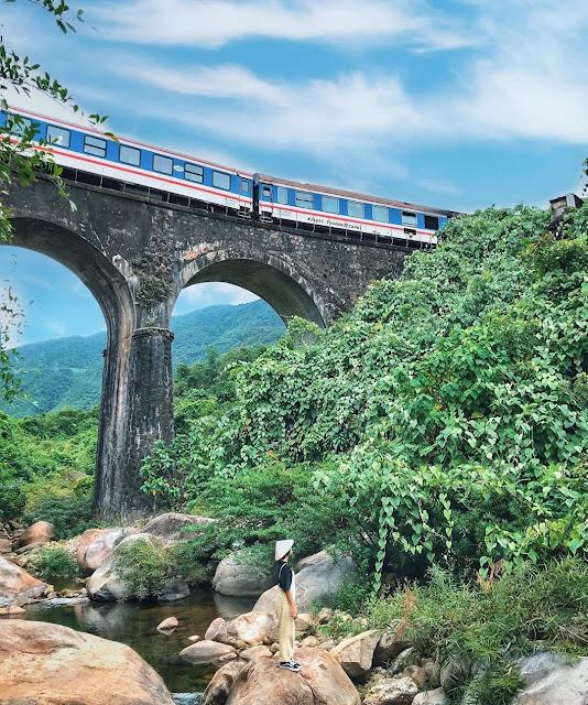 """Sau hành trình đi bộ 1 cây số, bạn sẽ thấy một cây cầu xe lửa với thiết kế mái vòm bắc qua con suối nhỏ trong veo tựa như một cánh cổng dẫn tới  xứ sở thần tiên. Đây chính là cây cầu vòm Đồn Cả. Dù đường đi tương đối """"khó nhằn"""" nhưng một khi được tận mắt nhìn thấy và đặt chân tới cầu vòm Đồn Cả, bạn sẽ cảm thấy chặng đường vừa trải qua hoàn toàn xứng đáng."""