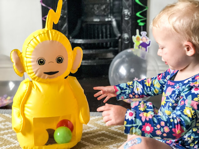 A toddler reaching towards an inflatable yellow teletubbie with balls in it's tummy