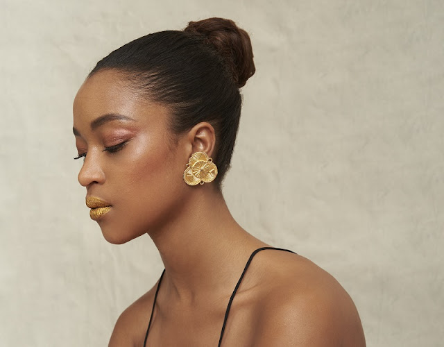 A model wearing gold earrings.