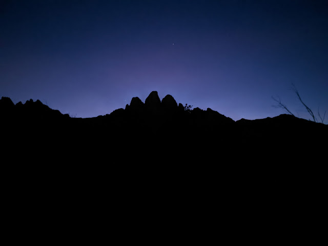 The sun all but gone behind the Organ Mountains. The mountains black, outlined by a small fringe of white lite that fades rapidly to deep blue and black.