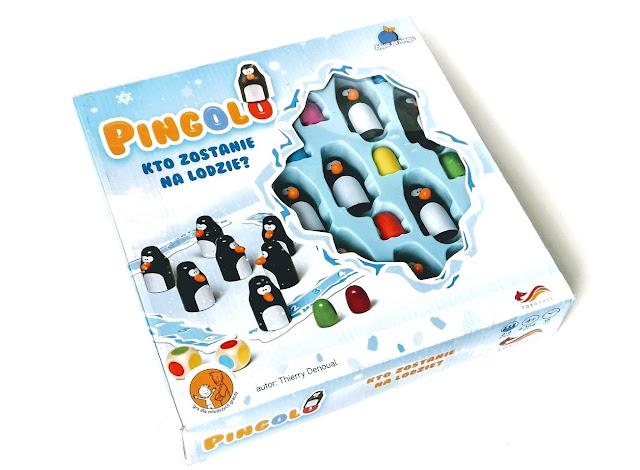 na zdjęciu opakowanie gry pingolo, na nim rysunki pingwinów, po środku pudełko ma okienko przez które widać wnętrze, błękitną wypraskę z umieszczonymi w niej pingwinami i kolorowymi jajami