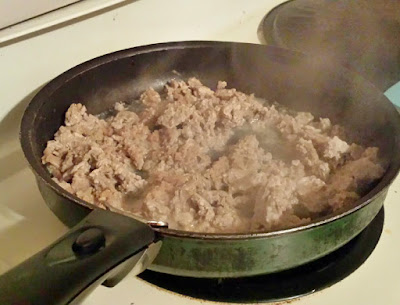Ground turkey frying in pan.