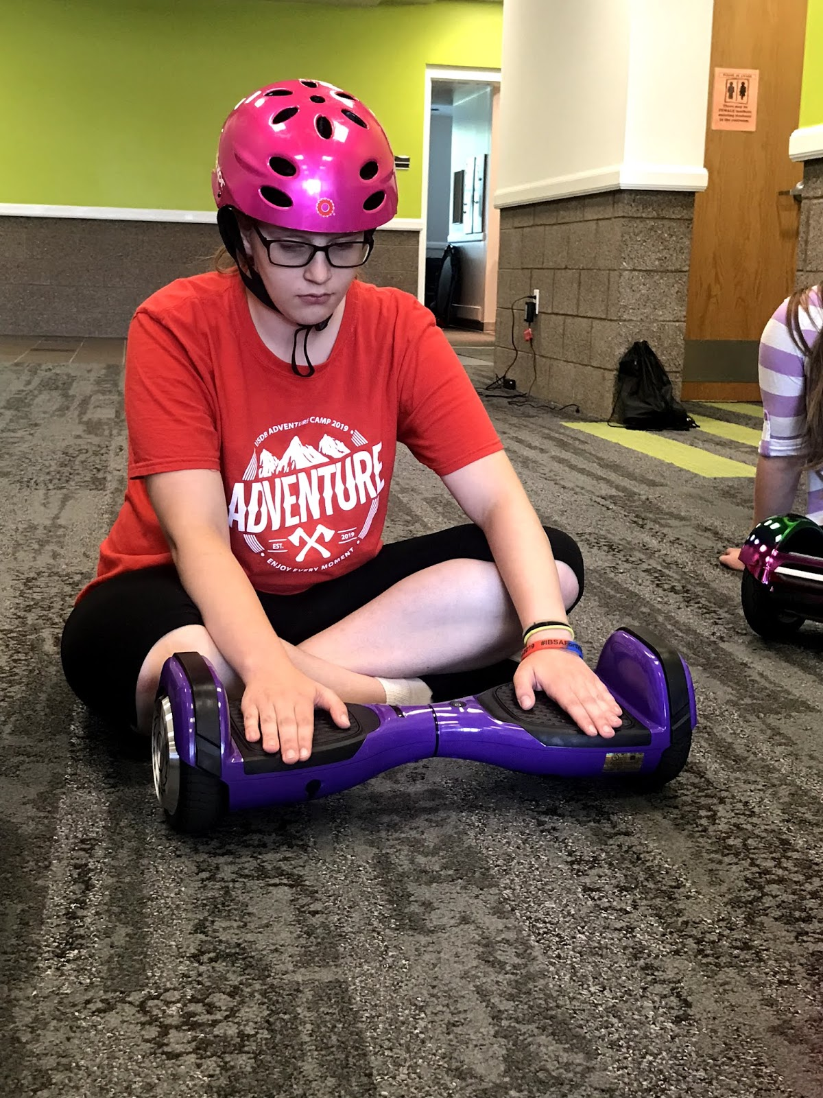 a female student sits on the ground and checks out the hoverboard