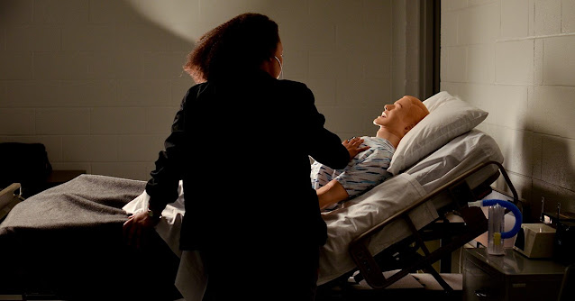 woman standing over a hospital bed with a dummy patient