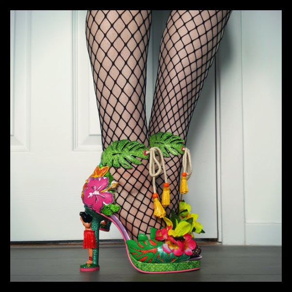 straight leg and bent leg in background wearing fishnet tights and Irregular Choice hula girl heeled shoes