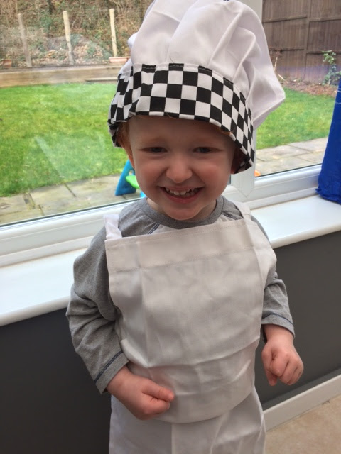 Little boy smiling whilst dressed as a chef