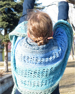A woman wearing a garter-stitch and lace crescent shawl across her back. The shawl is striped in a blue-green gradient.