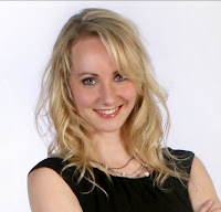 Headshot of author A.C. Anderson (sci-fi pen name for Alexia Chantel), blonde woman with blue eyes wearing a black dress.