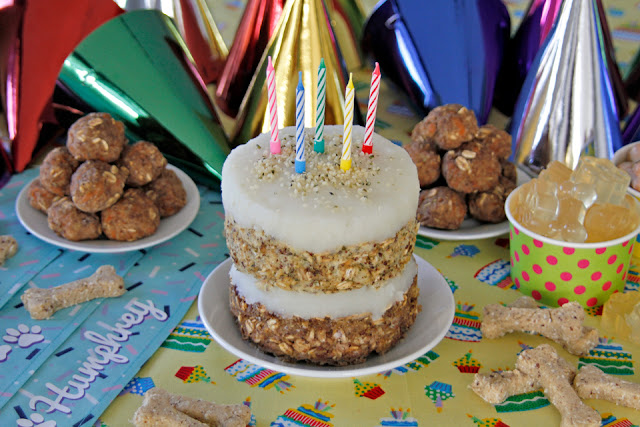 Homemade layered meatloaf dog birthday cake with potato frosting and candles on dog party buffet table.