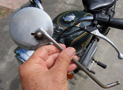Rear-view mirror with broken stalk in front of Royal Enfield.