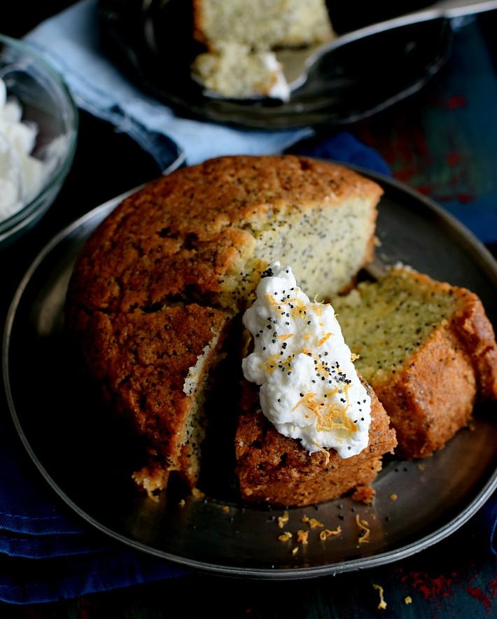 Torta con semillas de amapola y toronja, cortada en porciones, una de ellas decorada con crema batida